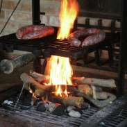 Nibbiano - Cooking sausages on the wood-burning grill